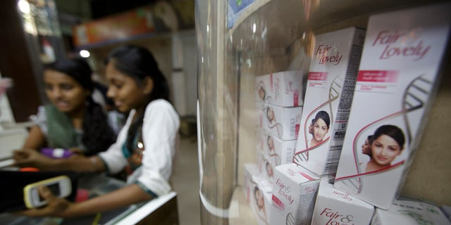 In this file photo, two young women stand at a counter next to a shelf where Hindustan Unilever Ltd. Fair & Lovely beauty products are displayed for sale at a store in Mumbai, India.