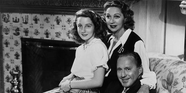 Family portrait of American comedian Jack Benny, his wife, Mary Livingstone, and their teenage daughter Joan Benny, seated together in a living room, circa 1945.