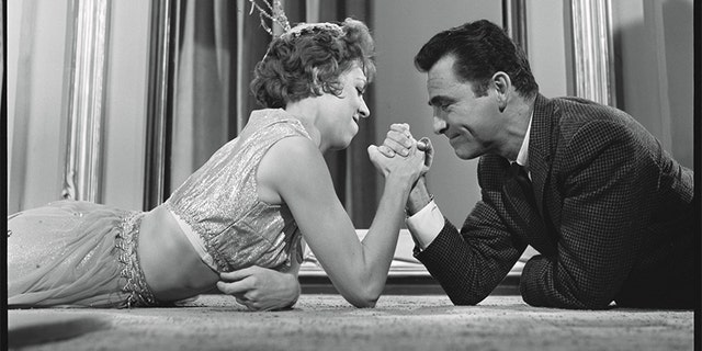 In an off-camera moment, Rod Serling arm wrestles with Carol Burnett.