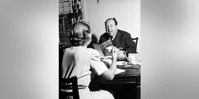 Alfred Hitchcock discussing his movie project with Joan Harrison at his apartment.