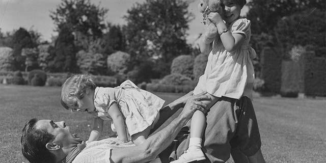 Portrait of actor Tyrone Power playing on the grass with his young daughters Romina (right) and Taryn, circa 1955.