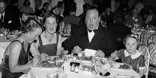 Alfred Hitchcock dining in a New York Restaurant with his wife Alma, his secretary Joan Harrison, and his daughter Patricia.
