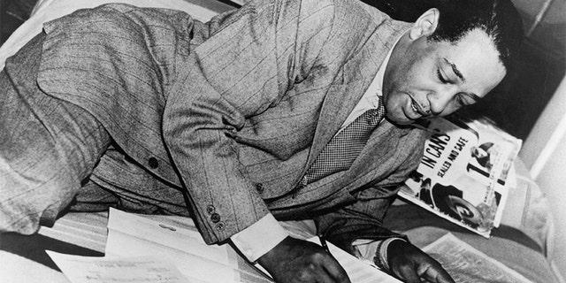 Duke Ellington writing on scores of music. Undated photograph.