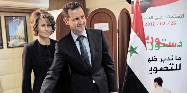 A handout picture released by the Syrian Arab News Agency (SANA) shows Syrian President Bashar al-Assad casting his ballot on the constitution that could end five decades of single-party domination, as his wife Asma looks on at a polling station in Damascus, on February 26, 2012. (AFP via Getty Images)