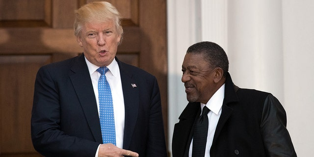 File Photo: President-elect Donald Trump greets Robert Johnson, the founder of Black Entertainment Television, at Trump International Golf Club, November 20, 2016 in Bedminster Township, New Jersey. (Photo by Drew Angerer/Getty Images)