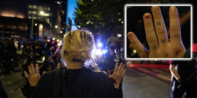 An image shows a woman raising her hands across from police – and in it tattoos on her knuckles are visible. Investigators said those tattoo matched ones they found on Channon when they searched her home. (DOJ)