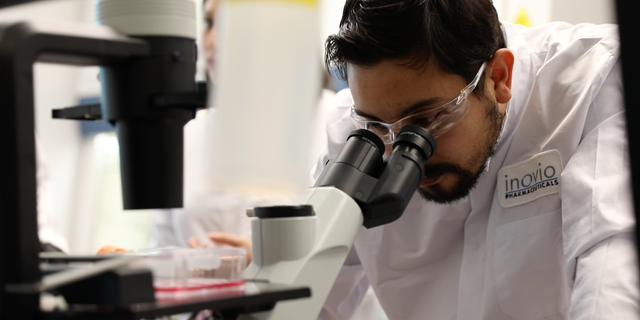 An INOVIO scientist peers into a microscope at the laboratory. (Photo courtesy of INOVIO Pharmaceuticals)
