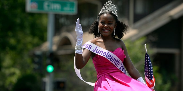 Miss Juneteenth 2015, Sean-Maree Swinger-Otey, 17, waves and joins in as neighbors and visitors line 23rd Ave. in Denver for the 6th annual Park Hill 4th of July Parade with more than 60 entries including the debut of the Park Hill Marching Band and a 16-foot tall replica of the Krishna temple.