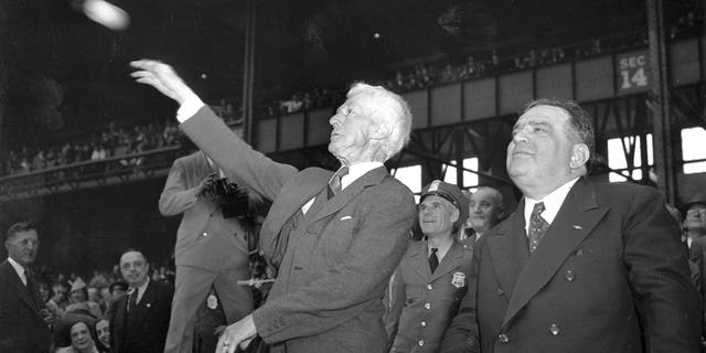 In this Oct. 1, 1941, file photo, Kenesaw Mountain Landis, baseball commissioner, throws out the first ball, formally opening the 1941 World Series featuring the Brooklyn Dodgers and the New York Yankees at Yankee Stadium, New York. (AP Photo)
