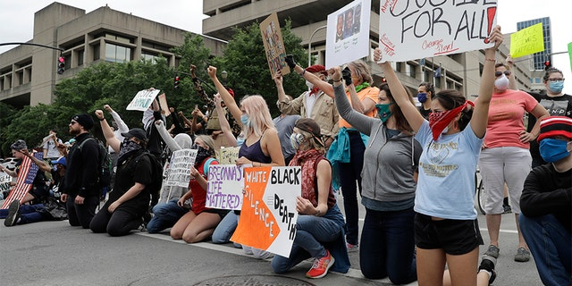 Protesters kneel in the middle of the street to block traffic as they protest the death of George Floyd and Breonna Taylor, Friday, May 29, 2020, in Louisville, Ky. Breonna Taylor, a black woman, was fatally shot by police in her home in March. (AP Photo/Darron Cummings)