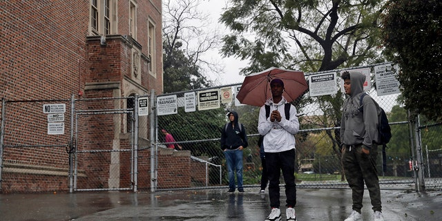 Students wait outside of John Marshall High School after being let out early following an announcement of a district-wide closure caused by the coronavirus threat in Los Angeles on March 13, 2020. (AP Photo/Marcio Jose Sanchez, File)
