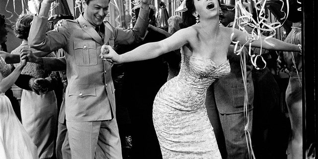 Argentine-American actress Linda Cristal, born Maria Victoria Moya Burges, goes wild at a party with American actor Tony Curtis, born Bernard Schwartz, in a scene from the movie, 'The Perfect Furlough,' by American director Blake Edwards. 1959. (Photo by Mondadori via Getty Images)