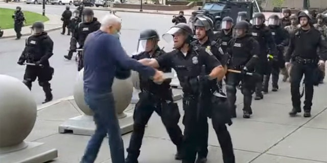 In this image from video provided by WBFO, a Buffalo police officer appears to shove a Martin Gugino who walked up to police. Video from WBFO shows the Gugino appearing to hit his head on the pavement, with blood leaking out as officers walk past to clear Niagara Square. Gugino's lawyer said Thursday that he suffered a brain injury. (Mike Desmond/WBFO via AP)