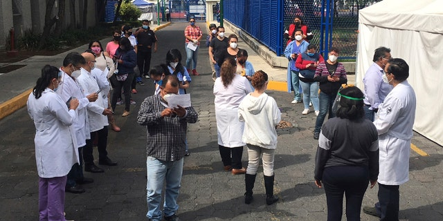Juarez public hospital health workers wait on a street after a 7.4 earthquake sent them out from their work areas, in Mexico City, Tuesday, June 23, 2020.