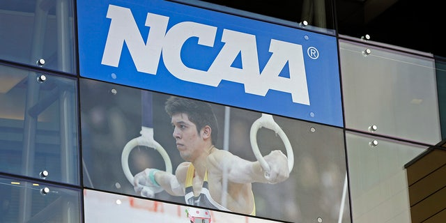 The NCAA logo and a gymnastics photo are seen outside the NCAA headquarters in Indianapolis, April 25, 2018. (Associated Press)