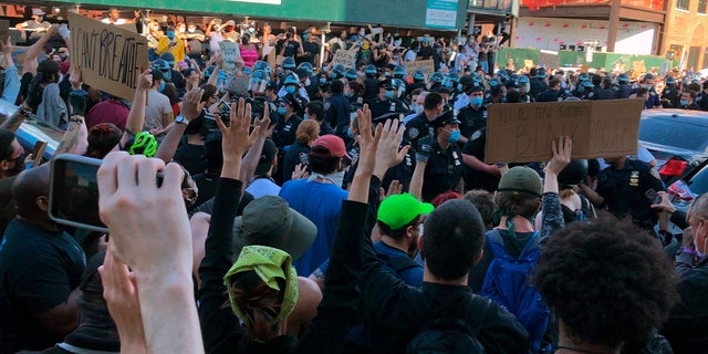 A large group of protesters surround members of the New York City Police Department in the Brooklyn borough of New York on Saturday. (AP)