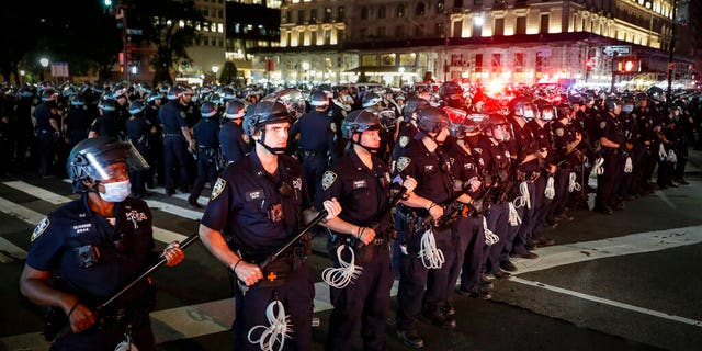 New York Police Department officers stand in formation after arresting multiple protesters marching after curfew on Fifth Avenue, Thursday, June 4, 2020, in New York. (AP Photo/John Minchillo)