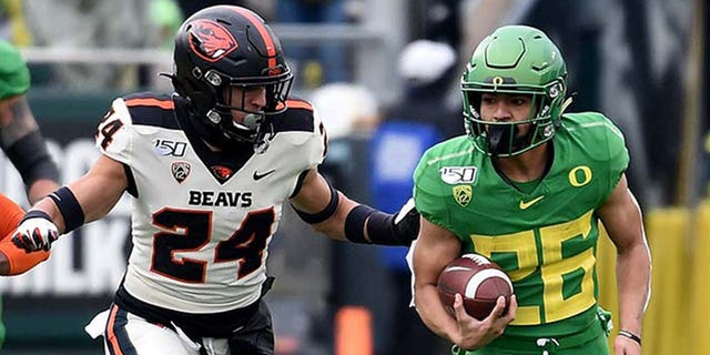 Running back Travis Dye #26 of the Oregon Ducks runs with the ball as defensive back David Morris #24 and defensive back Jaydon Grant #3 of the Oregon State Beavers give chase during the first half of the game at Autzen Stadium on November 30, 2019 in Eugene, 俄勒冈州. (Photo by Steve Dykes/Getty Images)