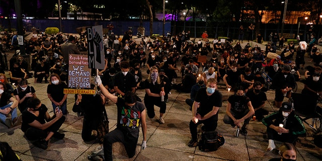 "Protesters kneel outside the U.S. Embassy during a peaceful demonstration denouncing racism and calling for justice for victims of police violence, in Mexico City, Thursday, June 4, 2020. Americans, Mexicans and other foreign nationals gathered in Paseo de la Reforma Thursday night, chanting ""Black lives matter"" and kneeling silently as the names of victims of violence were read aloud, including that of George Floyd, a black American man who died after being restrained by Minneapolis police officers on May 25. (AP Photo/Rebecca Blackwell)"