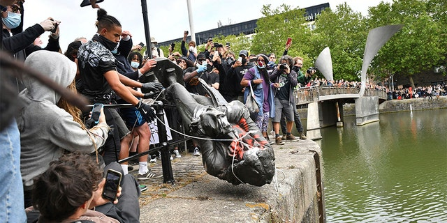 Protesters throw a statue of slave trader Edward Colston into Bristol harbor, during a Black Lives Matter protest rally in Bristol, England on Sunday. (AP/PA)