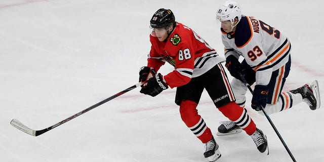 "In this March 5, 2020, file photo, Chicago Blackhawks right wing Patrick Kane, left, and Edmonton Oilers center Ryan Nugent-Hopkins chase the puck during the third period of an NHL hockey game in Chicago. Assuming everything goes according to plan and the final details are ironed out between the league and the players' union, the Blackhawks will play the Oilers in a best-of-five qualifier series for the playoff bracket. ""It's been a weird three months,"" Kane said during a video conference call with reporters. (AP Photo/Nam Y. Huh, File)"