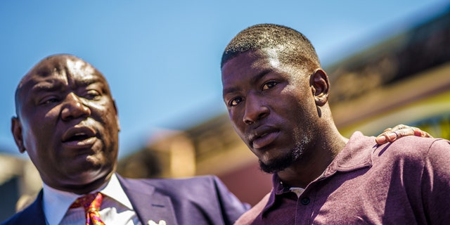 George Floyd's son, Quincy Mason Floyd (R) listens to family Attorney Ben Crump (L) speak to the press, as family members visit the site where George Floyd died, in Minneapolis, Minnesota, on June 3, 2020. (Photo by KEREM YUCEL/AFP via Getty Images)
