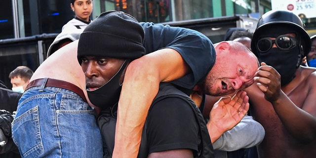A protester carries an injured counterprotester to safety, near the Waterloo station during a Black Lives Matter protest in London, Britain, June 13, 2020. (REUTERS/Dylan Martinez)