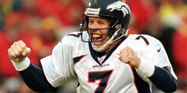 Denver Broncos quarterback John Elway celebrates a touchdown by teammate Terrell Davis.