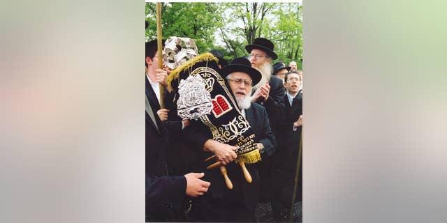 Rabbi Simcha Shafran, father of Rabbi Avi Shafran, carrying a Torah donated to a Baltimore synagogue.