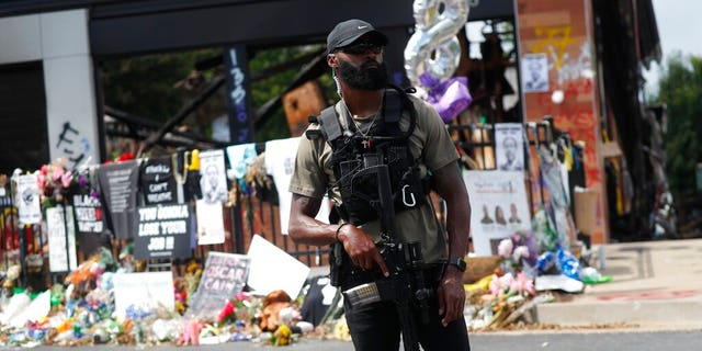 An armed protester awaits the casket of Rayshard Brooks to pass by the area where he was killed near a Wendy's restaurant on Tuesday, June 23, 2020, in Atlanta. (AP Photo/John Bazemore)