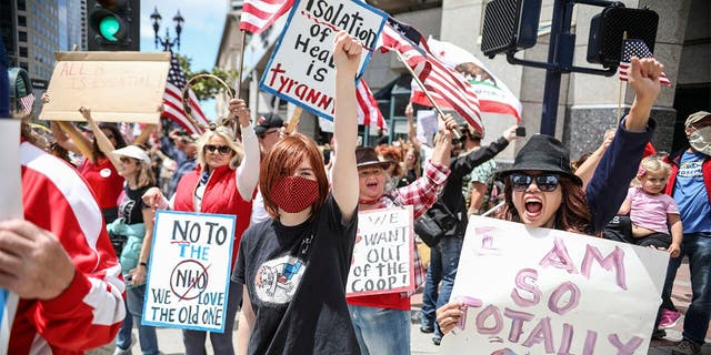 """Demonstrators protest during a """"Freedom Rally"""" against Stay-At-Home Directives on April 18, 2020 in San Diego, California."""