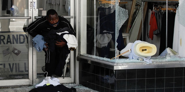 A man exits with clothing from a store Sunday, May 31, 2020, in Santa Monica, Calif., during unrest and protests over the death of George Floyd, who died after being restrained by Minneapolis police officers on May 25. (AP Photo/Marcio Jose Sanchez)