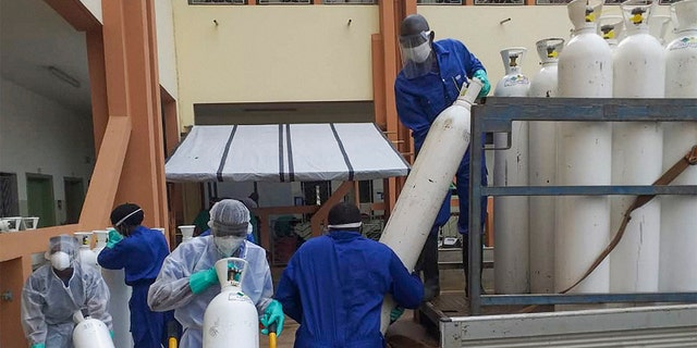 Medical workers offload cylinders of oxygen at the Donka public hospital where coronavirus patients are treated in Conakry, Guinea, on Wednesday, May 20, 2020. Before the coronavirus crisis,the hospital in the capital was going through20 oxygen cylinders a day. By May, the hospital was at 40 a day and rising, according to Dr.BillySivaheraofthe aid group Alliance for International Medical Action. Oxygenis the the facility's fastest-growingexpense, and the daily deliveries of cylinders are taking their toll on budgets. (AP Photo/Youssouf Bah)