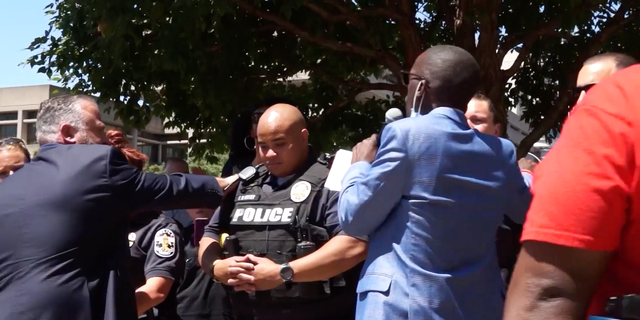 Pastor Brian Gibson prays over police officers with other faith leaders during a rally Tuesday in Louisville, Ky.
