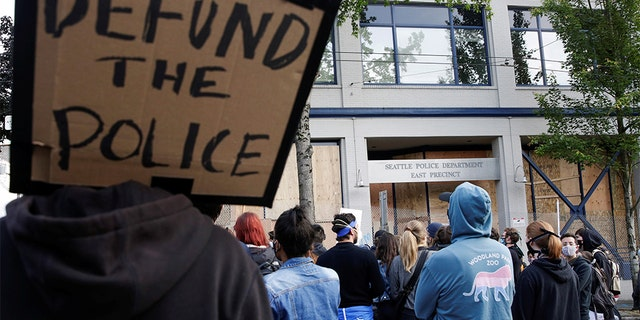 "A protester holds a sign that reads ""defund the police"" after Seattle Police vacated the department's East Precinct and people continue to rally against racial inequality and the death in Minneapolis police custody of George Floyd, in Seattle, Washington, U.S. June 8, 2020. (REUTERS/Jason Redmond)"