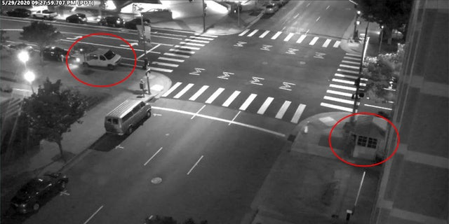 A still image taken from surveillance video outside the Oakland courhouse where David Patrick Underwood was abmushed and killed. The suspects' vehicle and the guard station have been circled in red. (DOJ)
