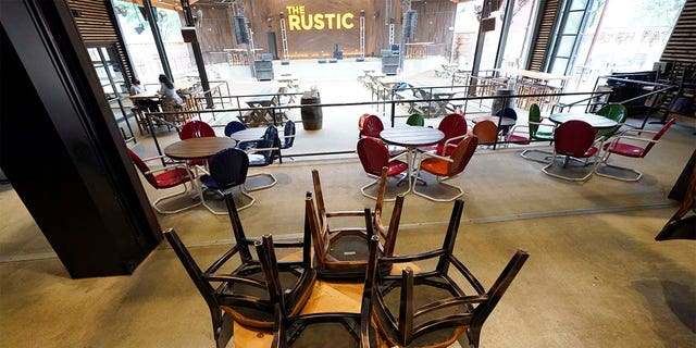 Chairs are stacked on a table inside The Rustic bar in Houston. The restaurant and bar will be limited to 50 percent capacity after Texas Gov. Greg Abbott announced Friday that he is shutting bars back down and scaling back restaurant capacity to 50 percent, in response to the increasing number of COVID-19 cases in Texas. (AP Photo/David J. Phillip)