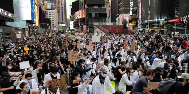 """Protesters kneel in Times Square in New York City on Tuesday. One of the city's Democrat councilmembers is claiming Tuesday that """"racism"""" -- and not large, tightly-packed gatherings like these -- would be to blame for any spike in coronavirus cases in the weeks ahead. (AP)"""