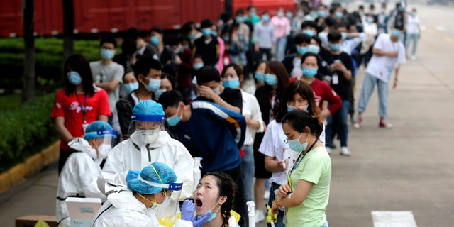 People line up for medical workers to take swabs for the coronavirus test at a large factory in Wuhan in central China's Hubei province on May 15, 2020. (Associated Press)