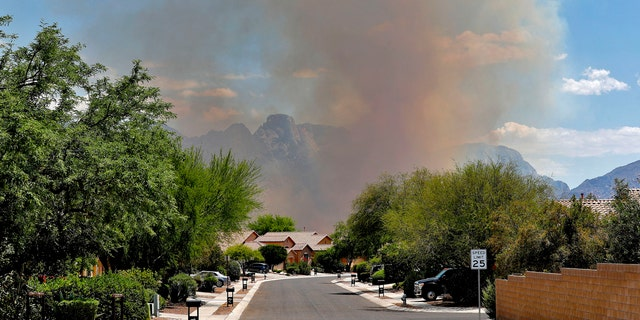 The Bighorn Fire backdrops a community along the western side of the Santa Catalina Mountains, Friday, June 12, 2020, in Tucson Ariz.