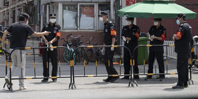 Security guards prepare for duty near a neighborhood under lockdown in Beijing on Tuesday. (AP)