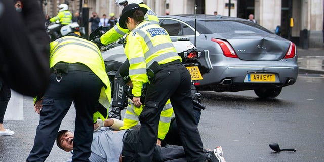 Police detained a man after he appeared to run in front of Johnson's car.  (Victoria Jones/PA via AP)