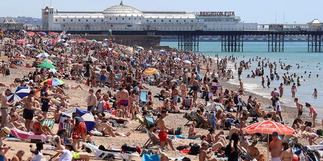 Crowds gather at the beach in Brighton, England, on Thursday. (Gareth Fuller/PA via AP)
