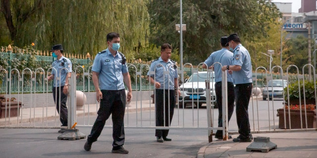 Police officers pull a barricade across a road leading to a residential neighborhood near the Xinfadi wholesale food market district in Beijing, Saturday, June 13, 2020.