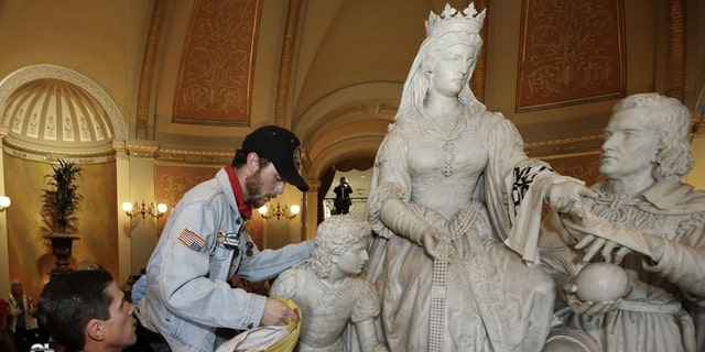 "In this June 4, 2018, file photo a demonstrator is removed from the statue of Queen Isabella and Christopher Columbus in the rotunda of the Capitol, by a California Highway Patrol officer, during a protest in Sacramento, Calif. Calling Columbus ""a deeply polarizing historical figure,"" Senate President Pro Ten Toni Atkins, D-San Diego; Assembly Speaker Anthony Rendon, D-Lakewood; and Assembly Rules Committee Chairman Ken Cooley, D-Rancho Cordova, announced Tuesday, June 16, 2020, that the controversial statue will be removed. (AP Photo/Rich Pedroncelli, File)"