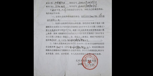 This Saturday, June 13, 2020 photo shows a January 2018 document telling Gulnar Omirzakh, a Chinese-born ethnic Kazakh, that she must pay a fine of 17,405 RMB ($2685) for having a third child, at her new home in Shonzhy, Kazakhstan. She says she was forced to get an intrauterine contraceptive device, and that Chinese authorities threatened to detain her if she didn't pay the fine for having a third child.