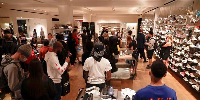 Customers walk inside the Selfridges department store in London on Monday. (AP)