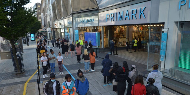 Shoppers queue up outside a Primark store as it reopened in Birmingham, England, on Monday. (AP/PA)