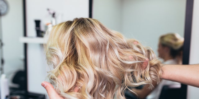 Beautiful hairstyle of young woman after dying hair and making highlights in hair salon.