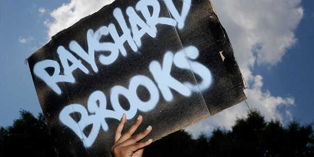 A protester holds up a sign on Saturday, June 13, 2020, near the Wendy's restaurant where Rayshard Brooks was shot and killed by police Friday evening following a struggle in the restaurant's drive-thru line in Atlanta. (Associated Press)